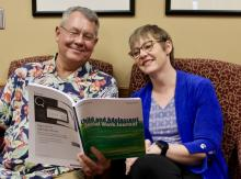 Bruce Thyer and Lisa Schelbe reading the Child and Adolescent Social Work Journal they co-edit.